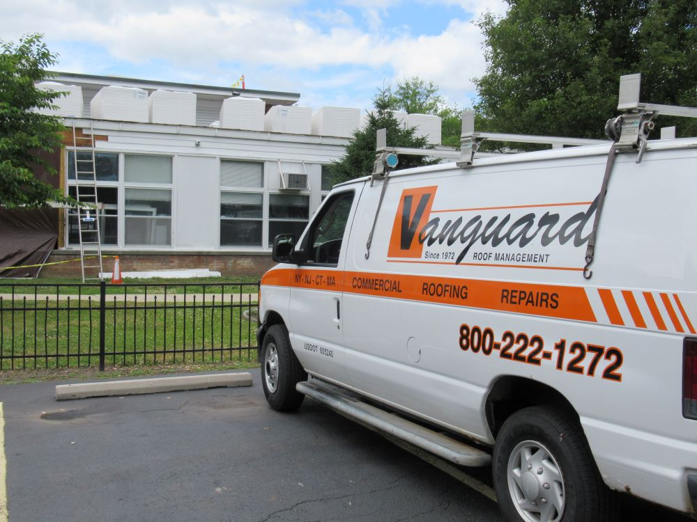 Vanguard roofing truck in front of commercial roof replacement job